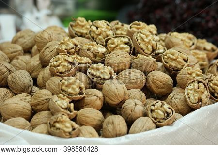 Close Up Of Walnuts At Farmers Market Stall. Farmers Market Walnuts In Shell For Sale. Food Industry
