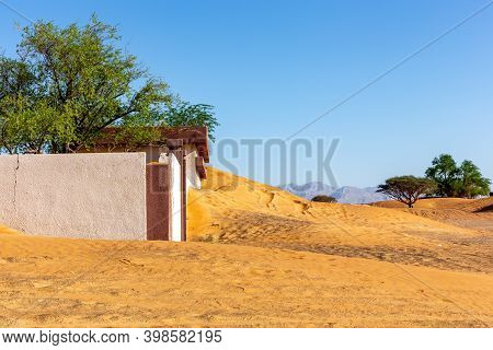 Abandoned Building And Fence Buried In Sand In Al Madam Ghost Village In Sharjah, United Arab Emirat