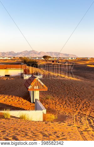 Al Madam Ghost Town Buildings And Courtyards Buried In Sand In The Desert, With Mountains In The Bac