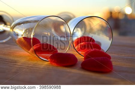 Two Glasses Of Champagne And Marmalade Red Hearts On The Wooden Table In Restaurant On Sunset Time,