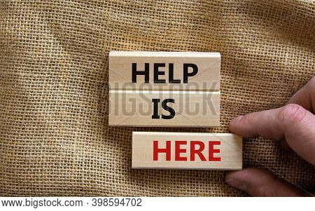 Help Is Here Symbol. Wooden Blocks With Words 'help Is Here'. Beautiful Canvas Background, Male Hand