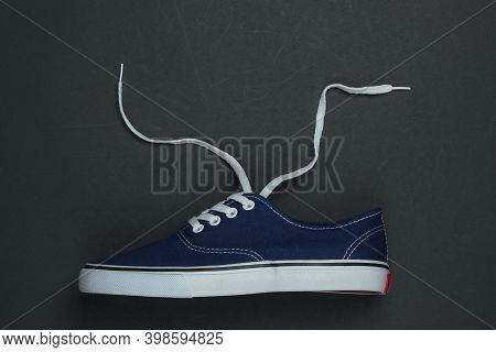 Classic Retro Sneaker With Untied Shoelaces On A Black Background. Top View. Crop Photo