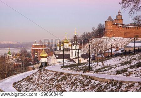 Orthodox Church And Nizhny Novgorod Kremlin In Winter At Pink Sunset