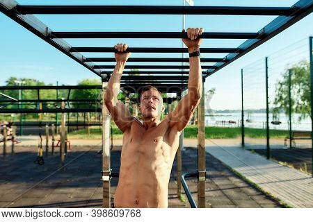 Young Powerful Caucasian Man Swinging On Skywalker During Street Workout On Sport Ground. Healthy Li