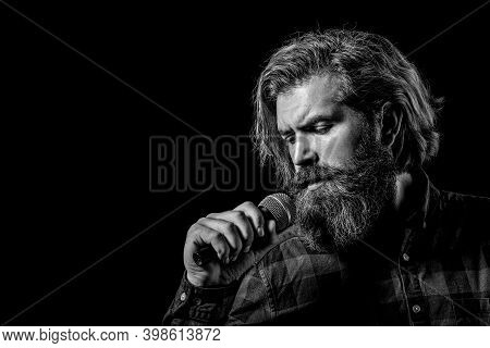 Male Singing With A Microphones. Bearded Man In Karaoke Sings A Song Into A Microphone. Male Attends