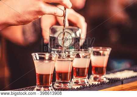 Shots At The Nightclub. Red Alcoholic Drink In Glasses On Bar. Red Cocktail At The Nightclub. Barman