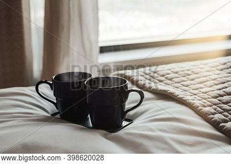 Two Black Coffee Cups On White Bed In Hotel Bedroom. Cozy Couple Weekend Concept Breakfast On Covere