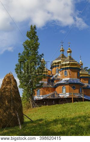 Beautiful Ancient Wooden Saint Nicholas Church In Koziova Villade On Picturesque Green Hill And Blue