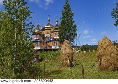 Beautiful Ancient Wooden Saint Nicholas Church In Koziova Villade On Forest Mountain Background. Car