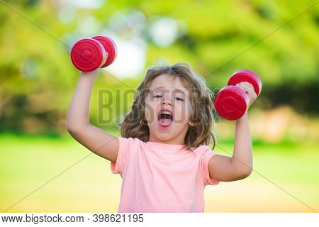 Funny Child Sport. Kid With Dumbbells In Park. Strong Little Boy. Fun Child Face. Fun Child Faces. F
