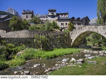 Mountain Village Built In Stone With A Bridge Over Which A River Flows On A Sunny Summer Day, Sallen