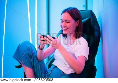 Gamer Girl In White T-shirt And Blue Jeans Holds Smart Phone In Hands And Plays Game App On Mobile P