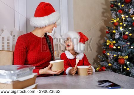 Mom And Her Little Daughter In Santa Helpers Costume Ordered Food And Grocery Delivery Over The Inte