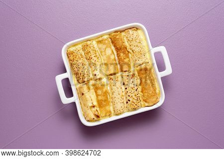 Top View With French Pancakes Rolls Stuffed With Curd Cheese Baked In A Tray With Sweet Cream Sauce.