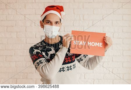 Happy Festive Man In Santa Hat, Protective Face Mask Hold Stay Home Banner In Hands. Cheerful Young