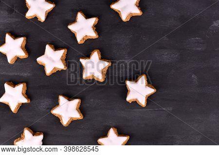 German Star Shaped Glazed Cinnamon Christmas Cookies Called 'zimtsterne' On Dark Black Ackground