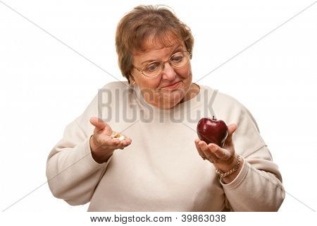 Confused Senior Woman Holding Apple and Vitamins Isolated on a White Background.