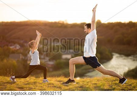 Father And Cute Daughter Doing Yoga Outside In Bright Sunny Day, Lovely Emotions. Together At Park.