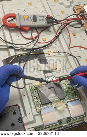Gloved Hands Of An Electrician Engineer Hold Multimeter Probe. Repair And Diagnostics Of Printed Cir