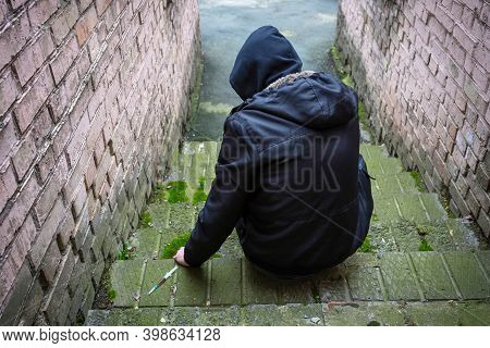 A Drug Addict, Alone, With A Syringe, Uses Drugs While Sitting On The Street. The View From The Back