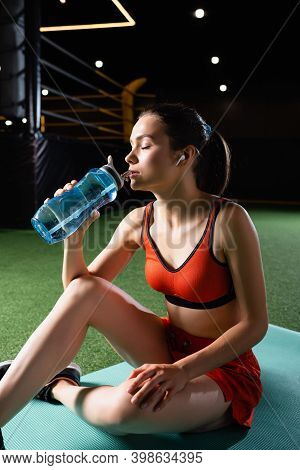 Thirsty Sportswoman With Earphone Drinking Water From Sports Bottle While Sitting On Fitness Mat Wit