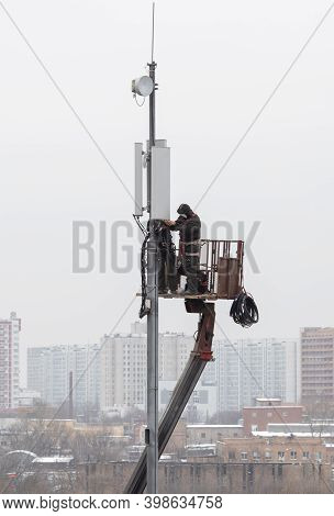 Technicians Install Mobile Signal Amplification Devices On Tower. It's Nasty. Unrecognizable People.