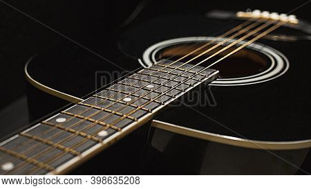 Fretboard, Strings And Acoustic Guitar On A Black Background