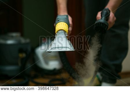 The Process Of Cleaning Carpets With A Steam Vacuum Cleaner. An Employee Of A Cleaning Company Holds