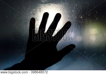 Help Me Please. A Hand Calling For Help On The Blurry Foggy Night Window. Symbol Of Helplessness