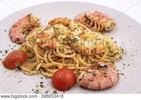 A Plate With Spaghetti And Prawns On A White Surface