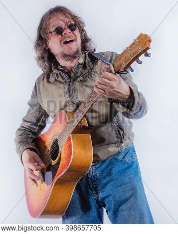 Mature Musician Plays Acoustic Guitar Studio Portrait.