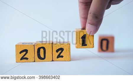 Wooden Block Calendar With A Focus On The Numbers 2021. There Is A Man's Hand Placing A Wooden Block