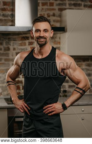 A Smiling Muscular Man With A Beard Is Posing With His Hands On A Waist In His Apartment After A Wor