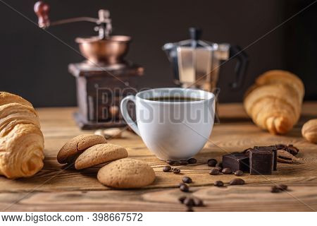 There Is Hot Black Coffee With Croissants, Cookies And Chocolate On A Wooden Table. There Is A Coffe