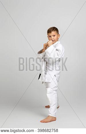 Little Child Boy In A White Karate Kimono. Karate Fighter Ready To Fight.