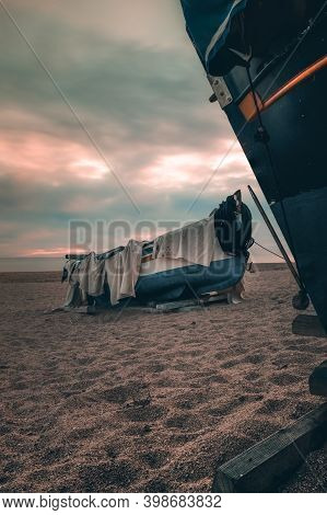 Abandoned Boat On The Beach Against  Soft Colorful Sunset Sky In Catalunya, Spain