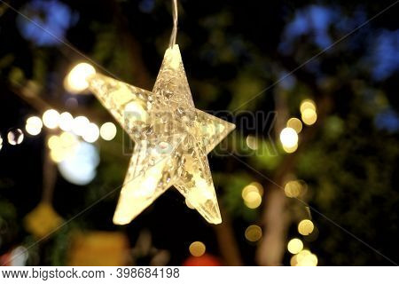 Blurred A Female Hand Holding A Star  Hanging Ornament Chirstmas Decoration With Light Bokeh In The