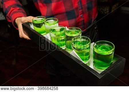 Waiter Holding A Set Of White-green Alcoholic Drinks Shots