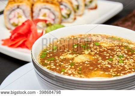 Japanese Miso Soup And Sushi Rolls On The Background