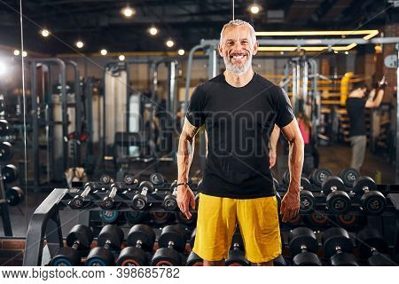 Joyous Personal Trainer Standing At The Gym
