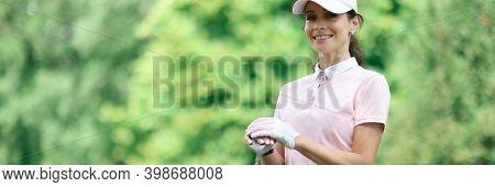 Woman Golfer Stands Next To Golf Course. Golf Equipment Concept