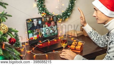Man With A Glass Of Champagne And A Red Santa Hat Is Wishing Merry Christmas To Friends Remotely Via