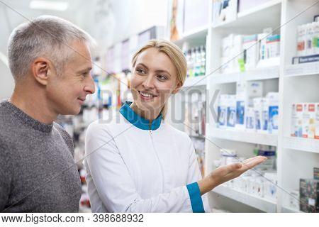 Friendly Female Chemist Helping Her Senior Male Customer, Showing Pharmacy Assortment On The Shelves