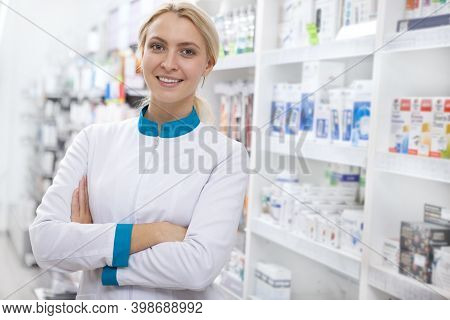 Cheerful Confident Female Pharmacist Smiling To The Camera With Her Arms Crossed, Posing Proudly At