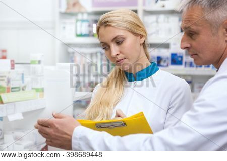 Lovely Young Female Pharmacist Working At The Drugstore With Her Senior Colleague, Examining Product