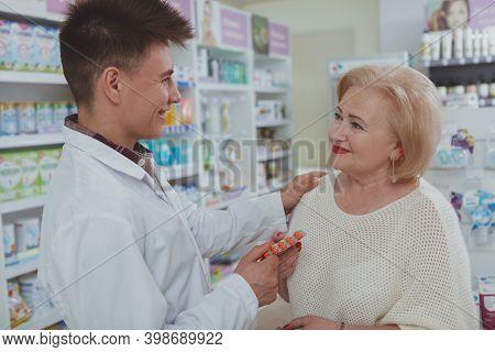 Lovely Senior Lady Buying Vitamins At The Drugstore. Friendly Cheerful Male Pharmacist Enjoying Work