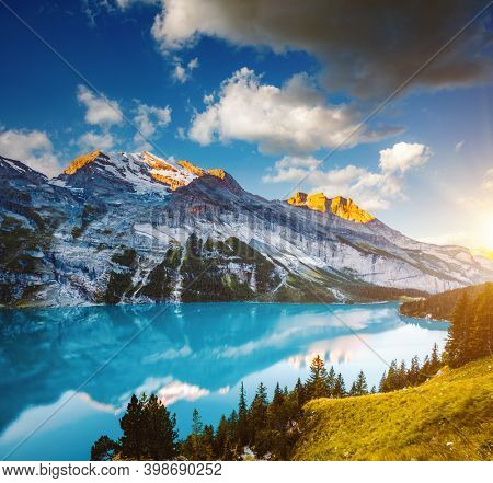 Awesome summer view of the lake Oeschinensee in sunny day. Location Swiss alps, Switzerland, Kandersteg district, Europe. Vivid photo wallpaper. Image of exotic place. Discover the beauty of earth.
