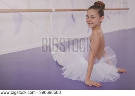 Beautiful Cheerful Little Ballerina Smiling To The Camera Over Her Shoulder, Resting At Ballet Schoo