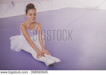 Happy Young Ballerina Girl Smiling To The Camera, Resting After Ballet Lesson, Copy Space. Beautiful