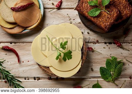 high angle view of some slices of vegan cheese, some tofu fillets and some cold cuts made of tofu, on a white rustic table